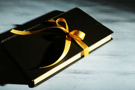 Book wrapped with color ribbon, on color wooden  background photo
