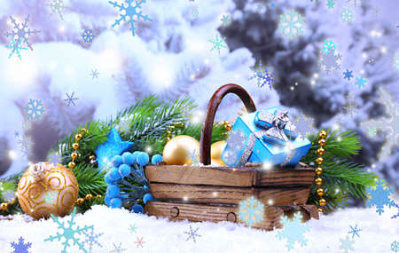 Composition with Christmas decorations in basket, fir tree on light background photo