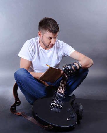 Young musician creating new melody for guitar on gray background photo