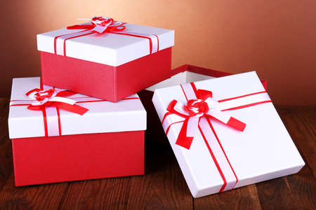 Beautiful gift boxes on table on brown background photo