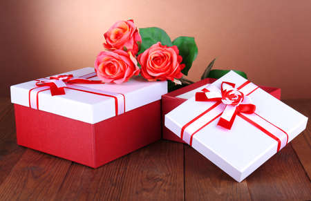 Beautiful gift boxes with flowers on table on brown background photo