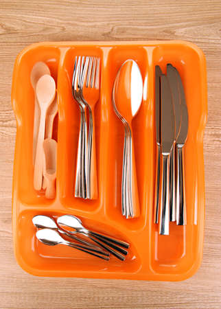seperated: Orange plastic cutlery tray with checked cutlery and wooden spoons on wooden table