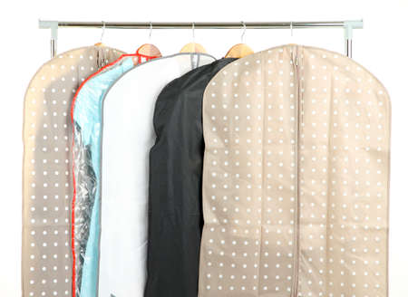 storing: Clothes in cases for storing on hangers, isolated on white Stock Photo