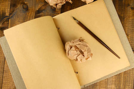Crumpled paper balls with notebook and ink pen on wooden background photo