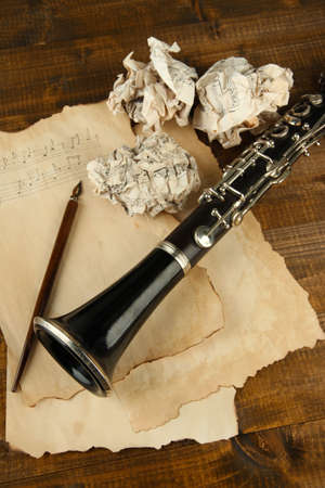 Crumpled paper balls with music sheets and clarinet on wooden background photo