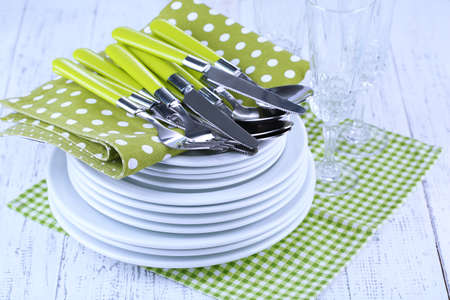 Clean dishes on wooden table on light background photo