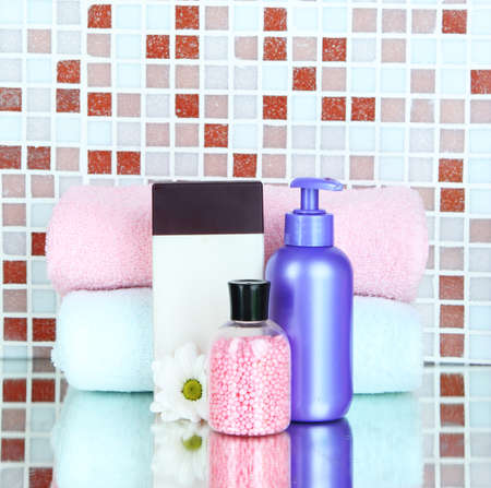 Cosmetics and bath accessories on mosaic tiles background photo