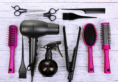 hair design salon: Hairdressing tools on white wooden table close-up