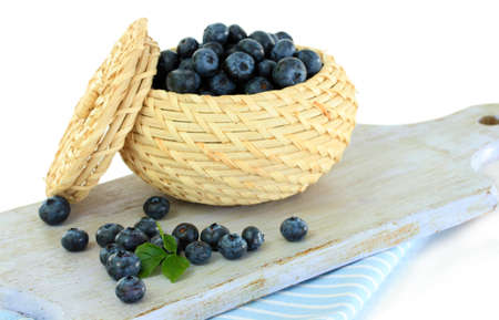 Blueberries in wooden basket on board on napkin isolated on white photo