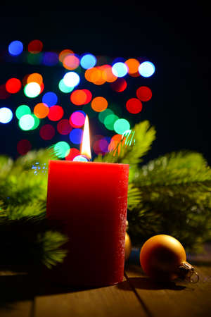 Composition with Burning candle, fir tree and Christmas decorations on multicolor lights background photo