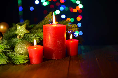 Composition with burning candles, fir tree and Christmas decorations on multicolor lights background photo