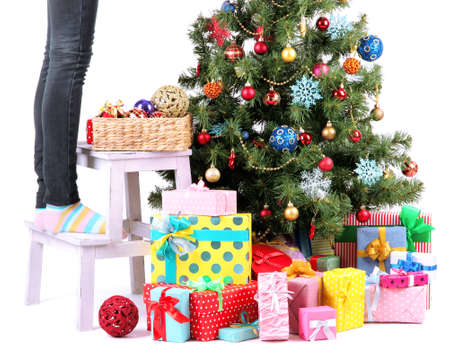 Female legs on wooden ladder near Christmas tree and gifts isolated on white photo