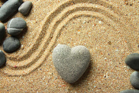 Grey zen stone in shape of heart, on sand photo
