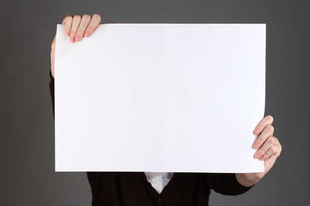 Woman holding blank sign in front her face Imagens