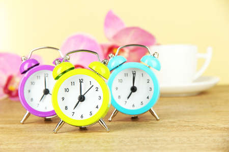Colorful alarm clock on table on beige background photo