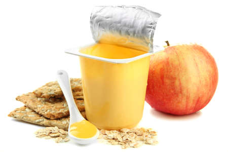 Tasty yogurt in open plastic cup, cookies and fruit, isolated on white photo
