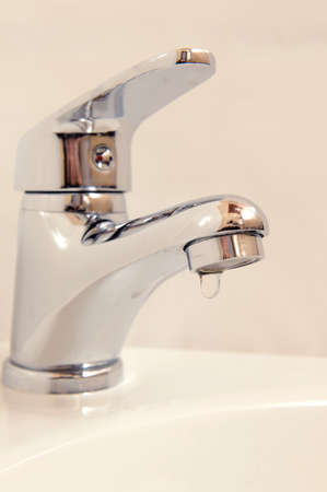 Close-up of human hands being washed under faucet in bathroom photo