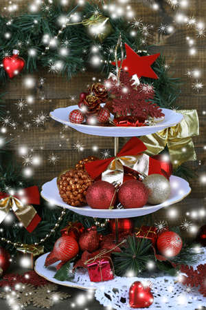 Christmas decorations on dessert stand, on wooden background photo