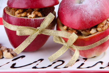Stuffed apples with nuts and raisins on plate close up photo