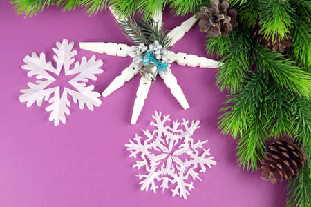 Beautiful snowflakes with fir branch on purple background photo