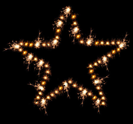 Christmas sparklers in shape of star on black\ background