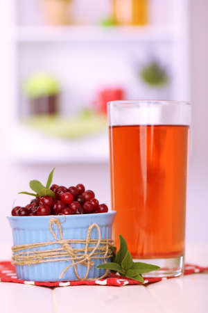 Glass of cranberry juice and ripe red cranberries in bowl on table  photo