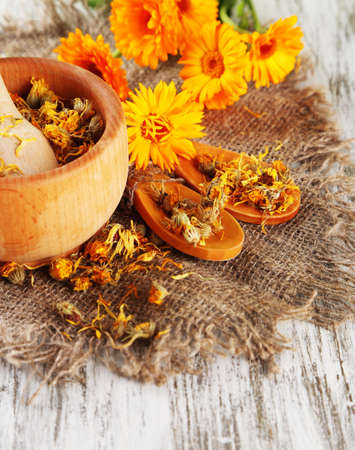Fresh and dried calendula flowers in mortar on wooden background