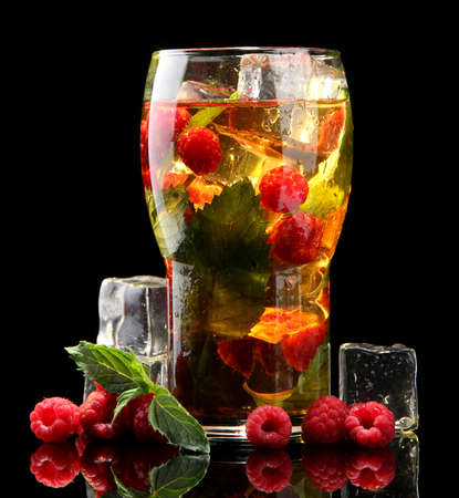 Iced tea with raspberries and mint on black background  photo