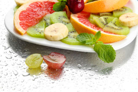 Assortment of sliced fruits on plate with drops photo