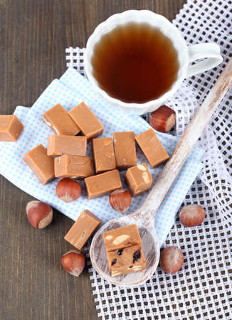 Many toffee in spoon and cup of tea on napkins on wooden table photo