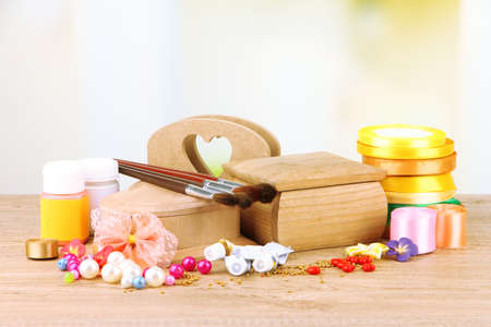 Handmade wooden boxes and art materials for decor, on table photo