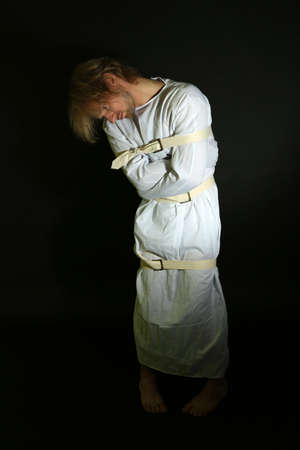 Mentally ill man in strait-jacket on black background photo