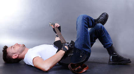 Young musician playing  guitar on gray background photo