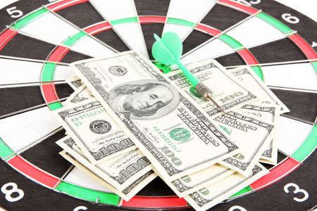 Dart on dartboard and money close up. Concept of success. photo