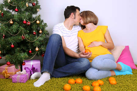 Young pregnant woman with her husband sitting on floor near Christmas tree at home  photo