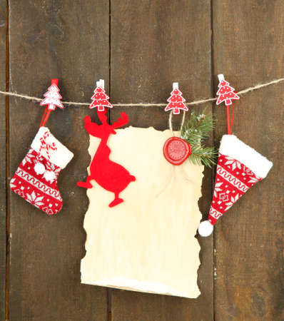 Blank sheet with Christmas decor hanging on grey wooden wall photo