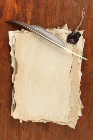 Old paper and feather on wooden background photo