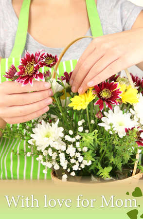 Florist makes flowers bouquet in wicker basket photo