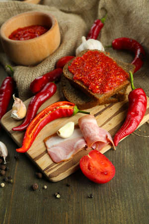 Composition with salsa sauce on bread,, red hot chili peppers and garlic, on sackcloth, on wooden background