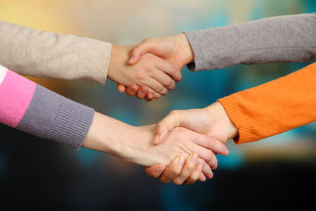 manos estrechadas: Los apretones de manos en el fondo brillante Foto de archivo