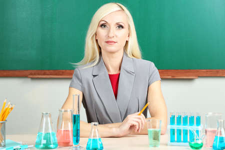 Chemistry teacher sitting at table on blackboard background photo
