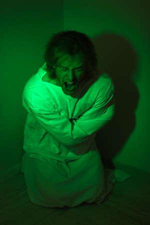 Mentally ill man in strait-jacket in room corner photo