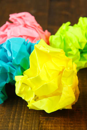 wastrel: Colorful crumpled paper balls on wooden background Stock Photo