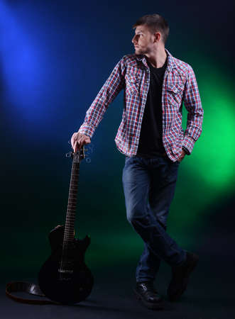 Young musician with guitar on dark color background photo