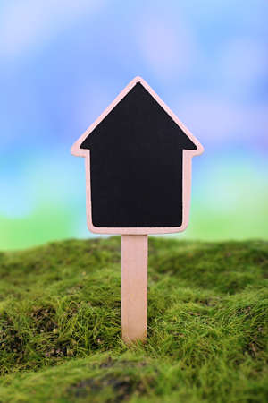 Small chalk board on grass on light background photo