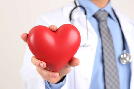 Male Doctor with red heart in his hands, isolated on white background photo