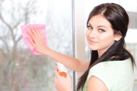 Beautiful young woman washing window in room