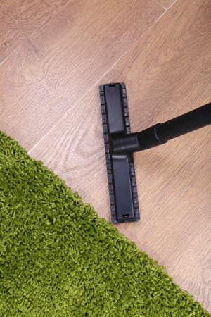 Vacuuming carpet in house photo