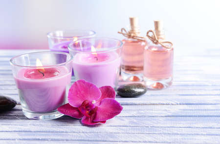 candlelit: Beautiful colorful candles, spa stones and  orchid flower,on color wooden table, on light background Stock Photo