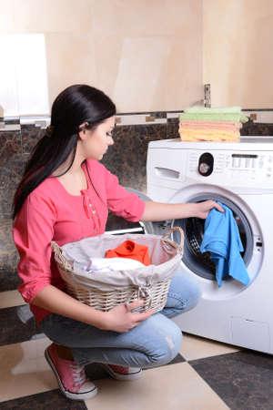 lavando ropa: Mujer joven hermosa que borra en casa